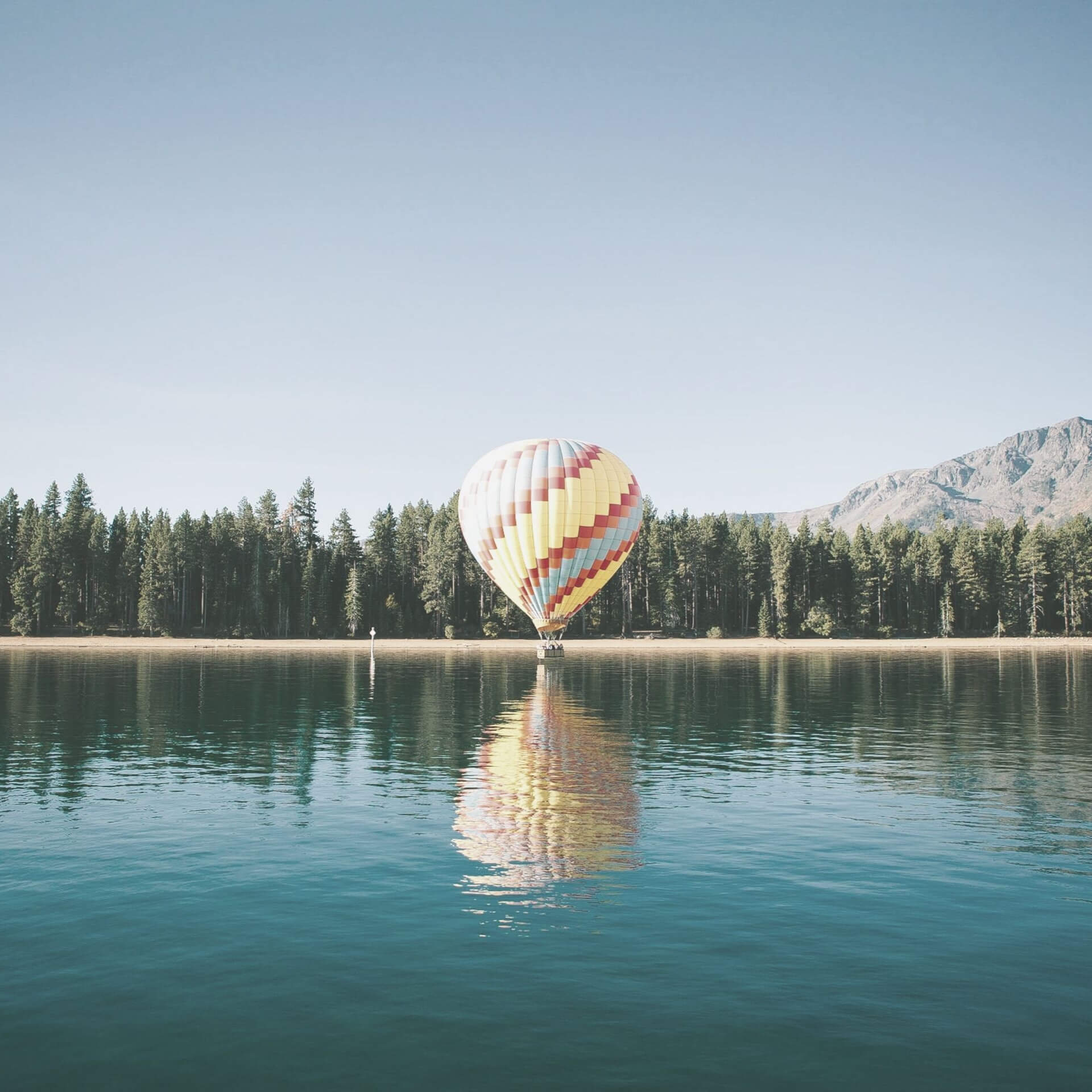 power of tourism advertising: a hot air balloon touching down on the surface of a lake.