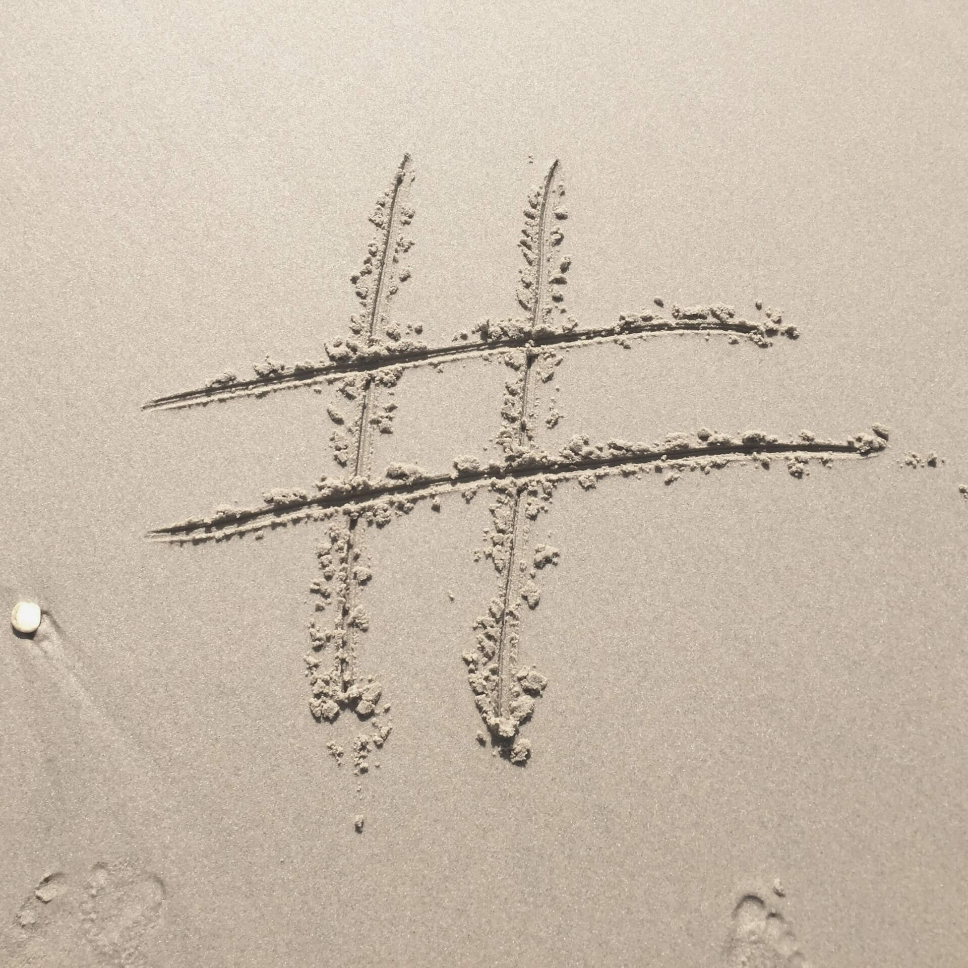 Instagram hashtags tips: hashtag drawn in sand on a beach