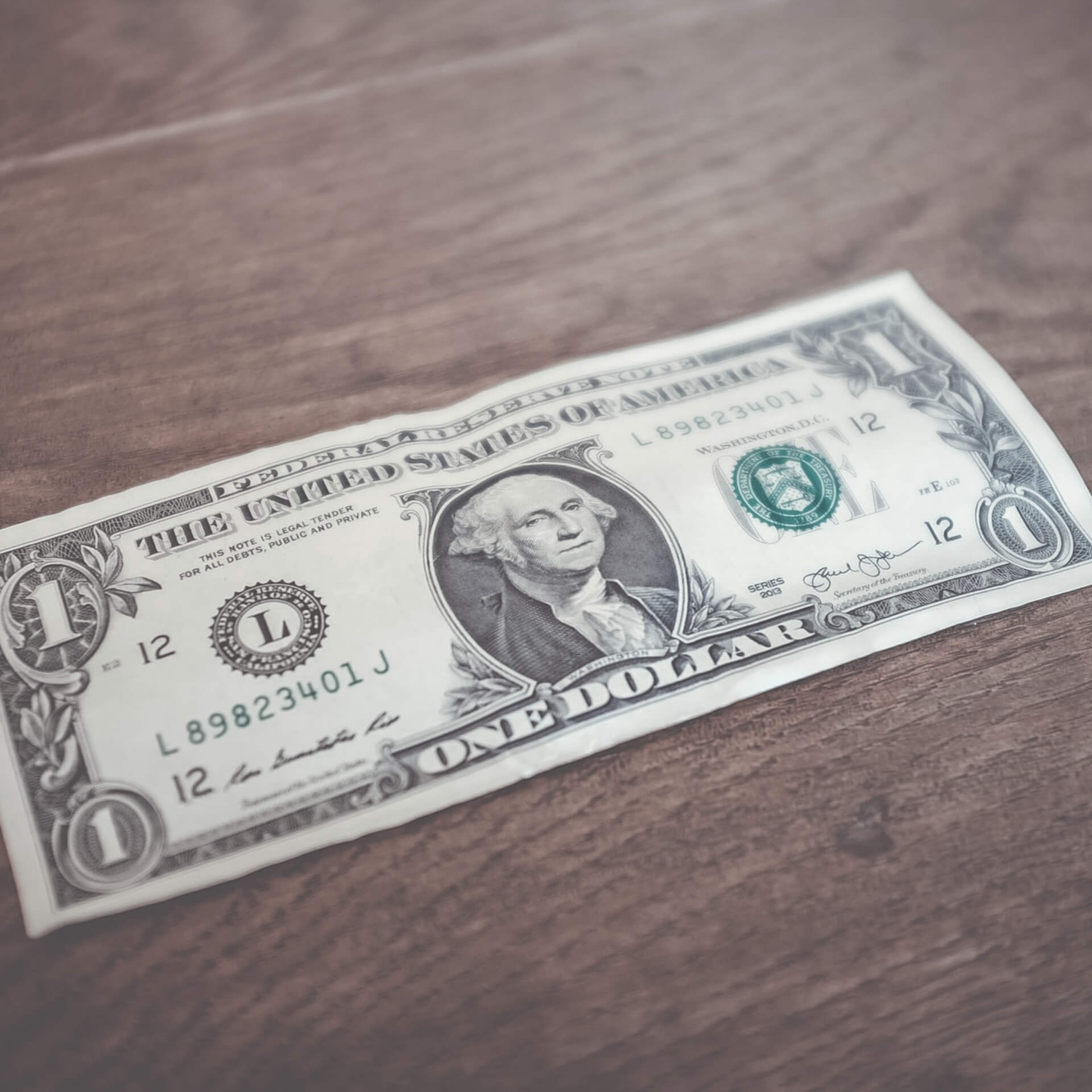 reacting nonprofit donors: One dollar bill face up on a brown wooden table.