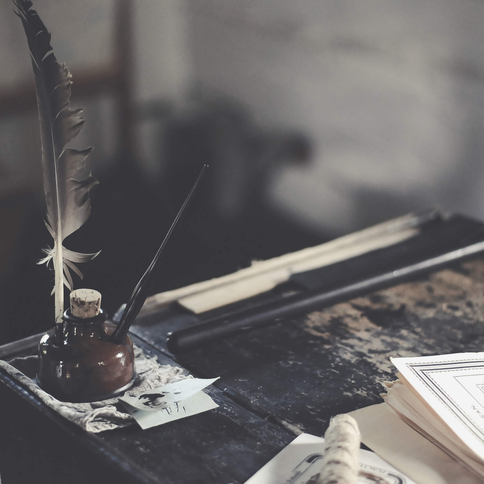 writing tips to improve digital marketing strategy: Feather quill resting in an ink well on and old desk