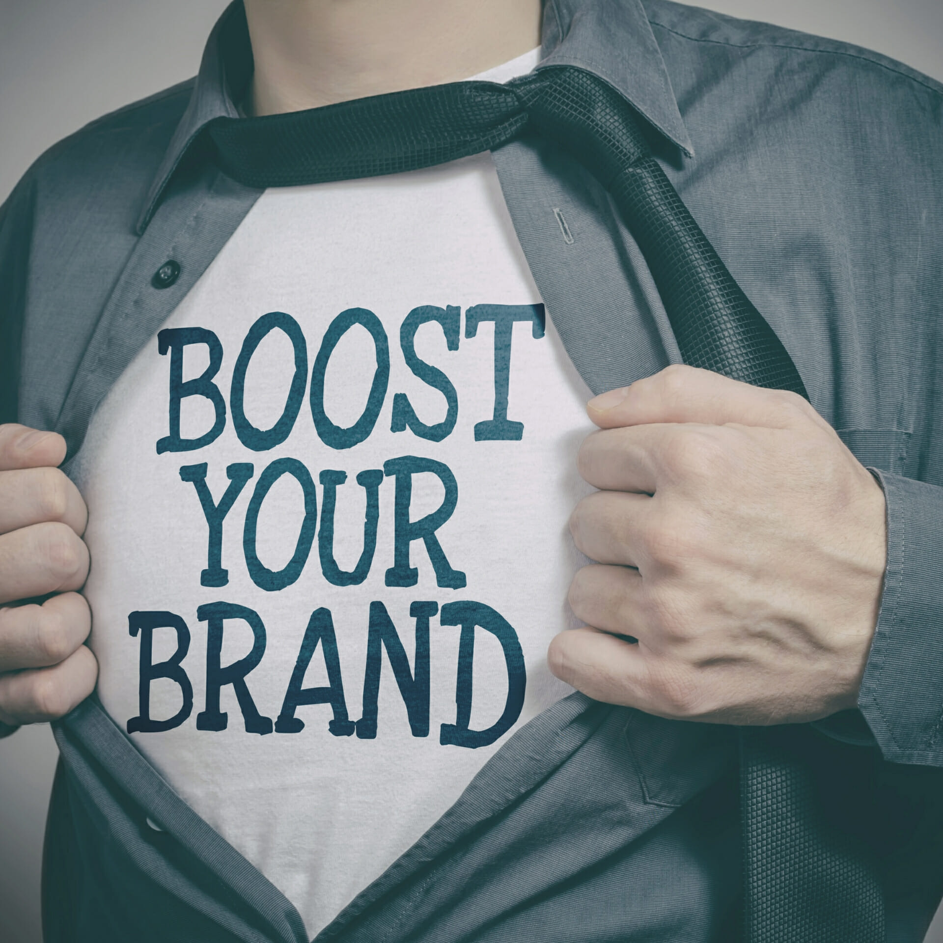 "branding words: man pulling open his shirt 'superman style' to reveal a t-shirt that says ""Boost your brand"""