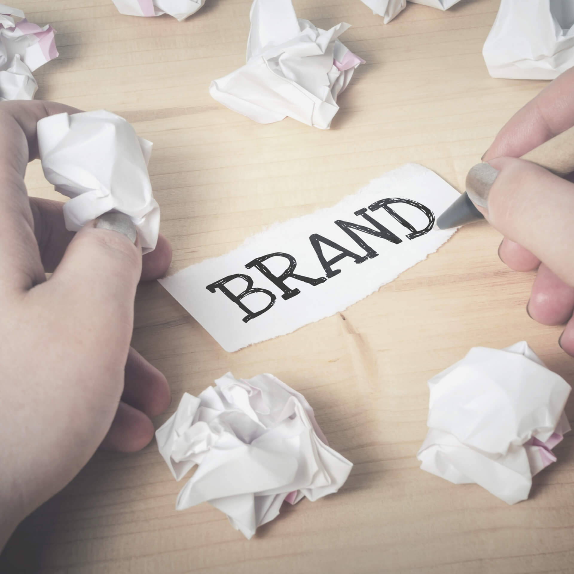 "insider branding tips: hands drawing out the word ""brand"" surrounded by crumpled up pieces of paper."