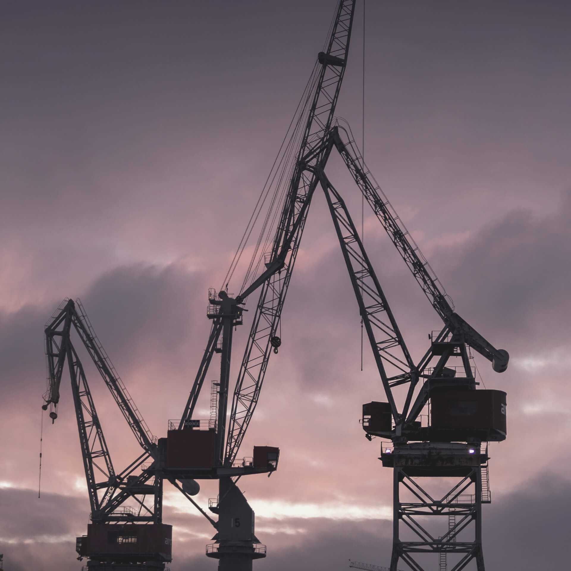 build a brand small business: construction cranes in front of blue and purple clouds
