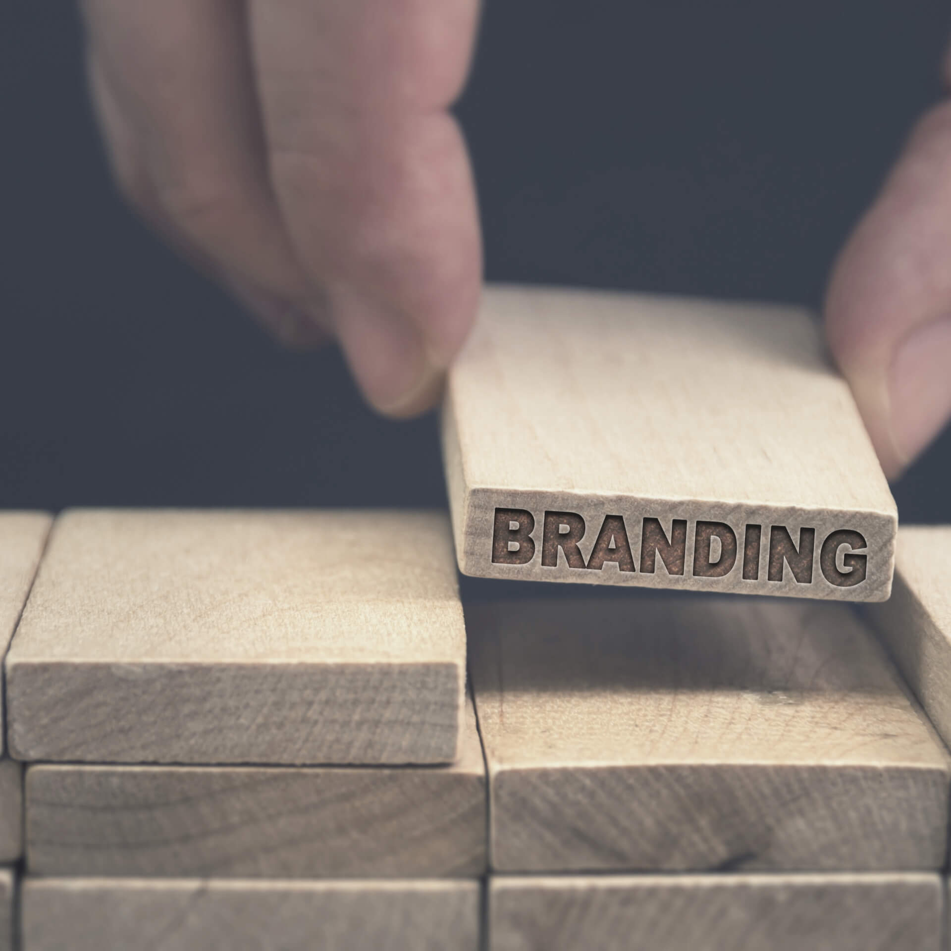"nonprofit branding strategy: person placing a missing piece to a stack of wood. Missing piece is labeled ""branding"""