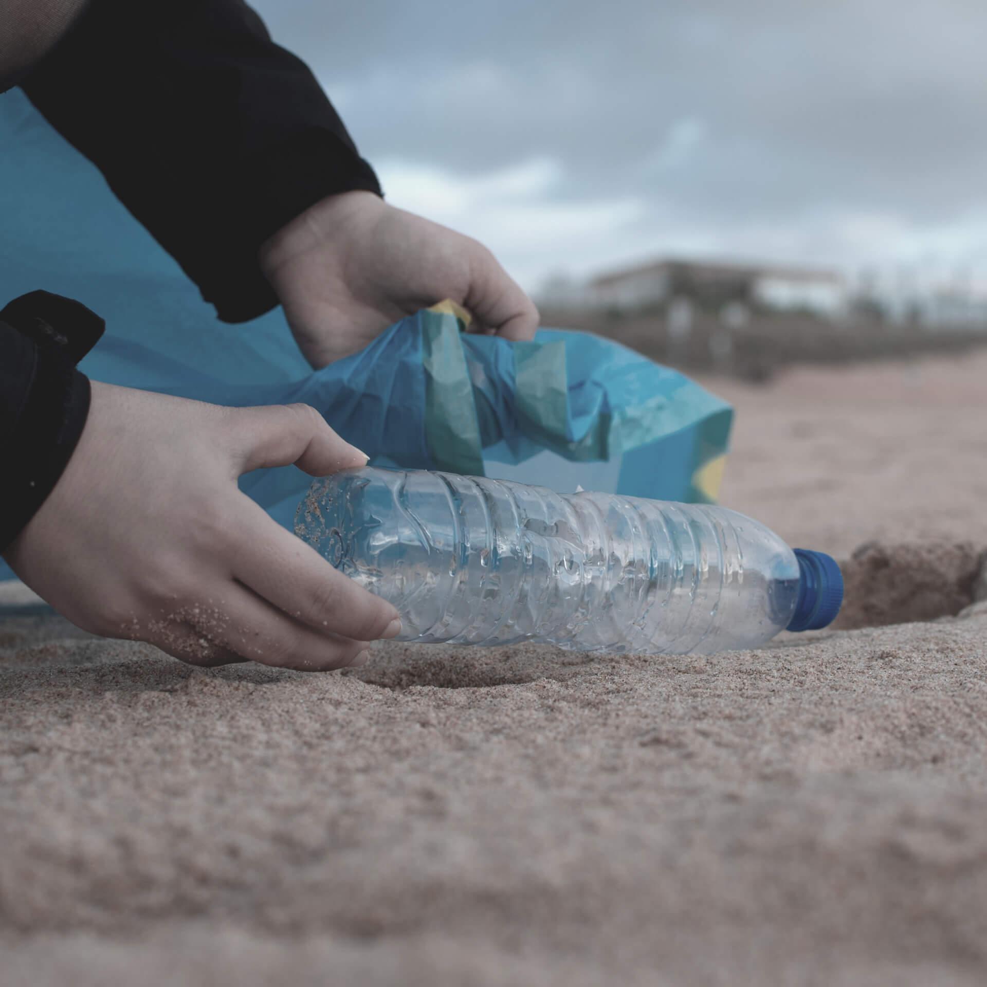 SEO marketing benefits: Volunteer picking up trash at the beach.