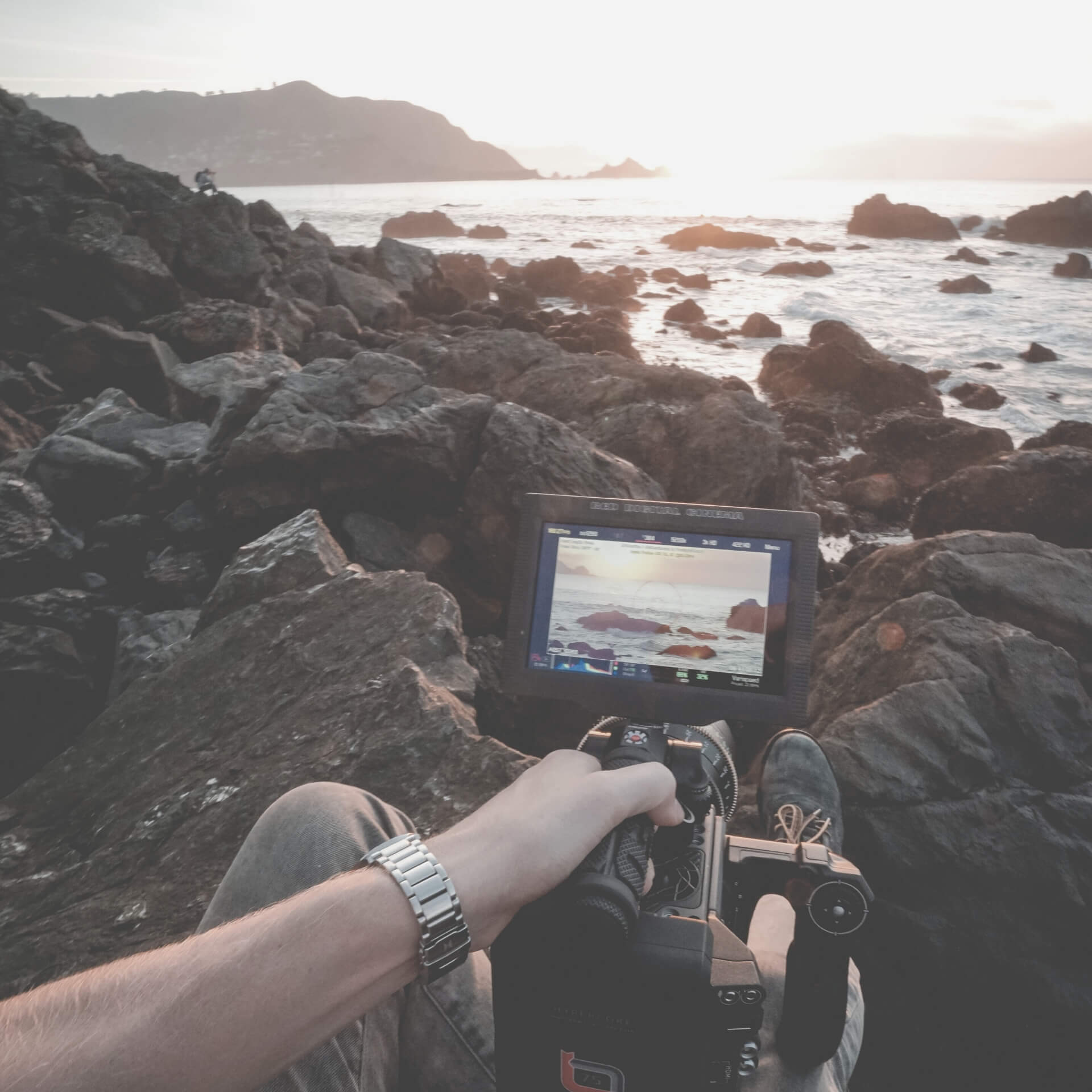 Create Marketing Videos: Person on a rock beach filming the ocean.