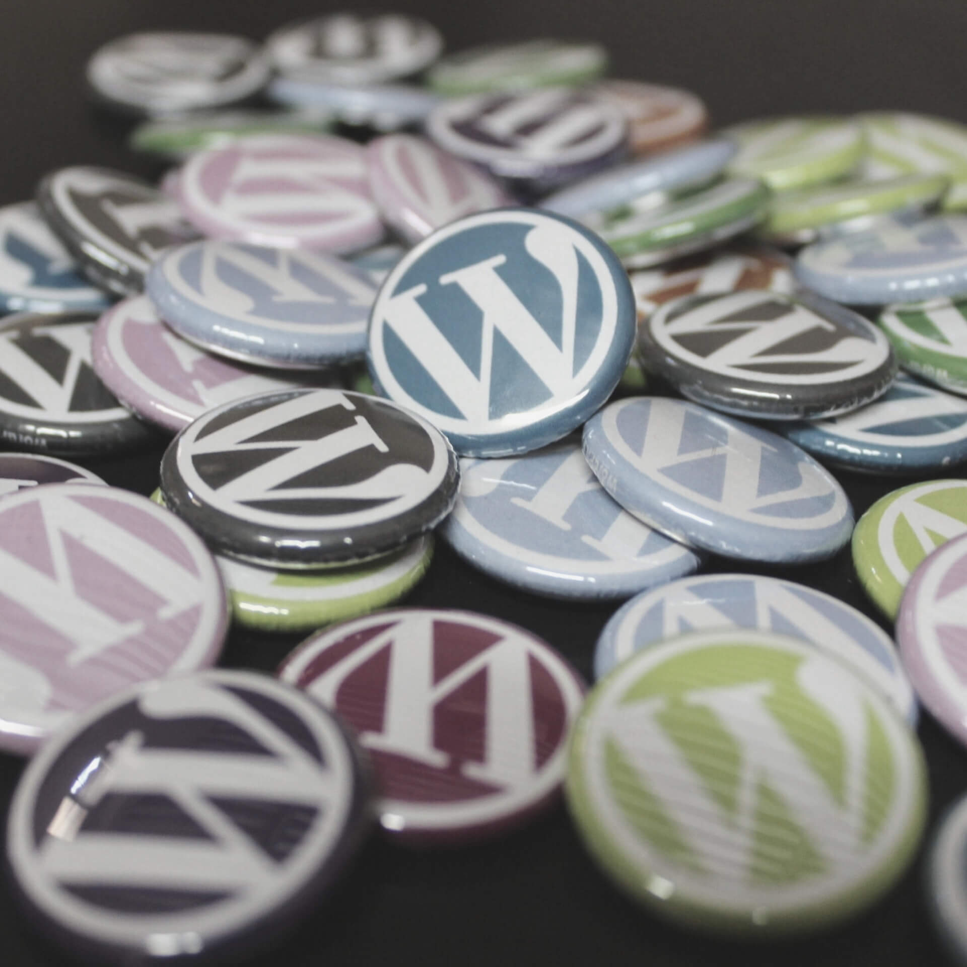 WordPress for Business: A pile of multicolors buttons with the WordPress logo on them.