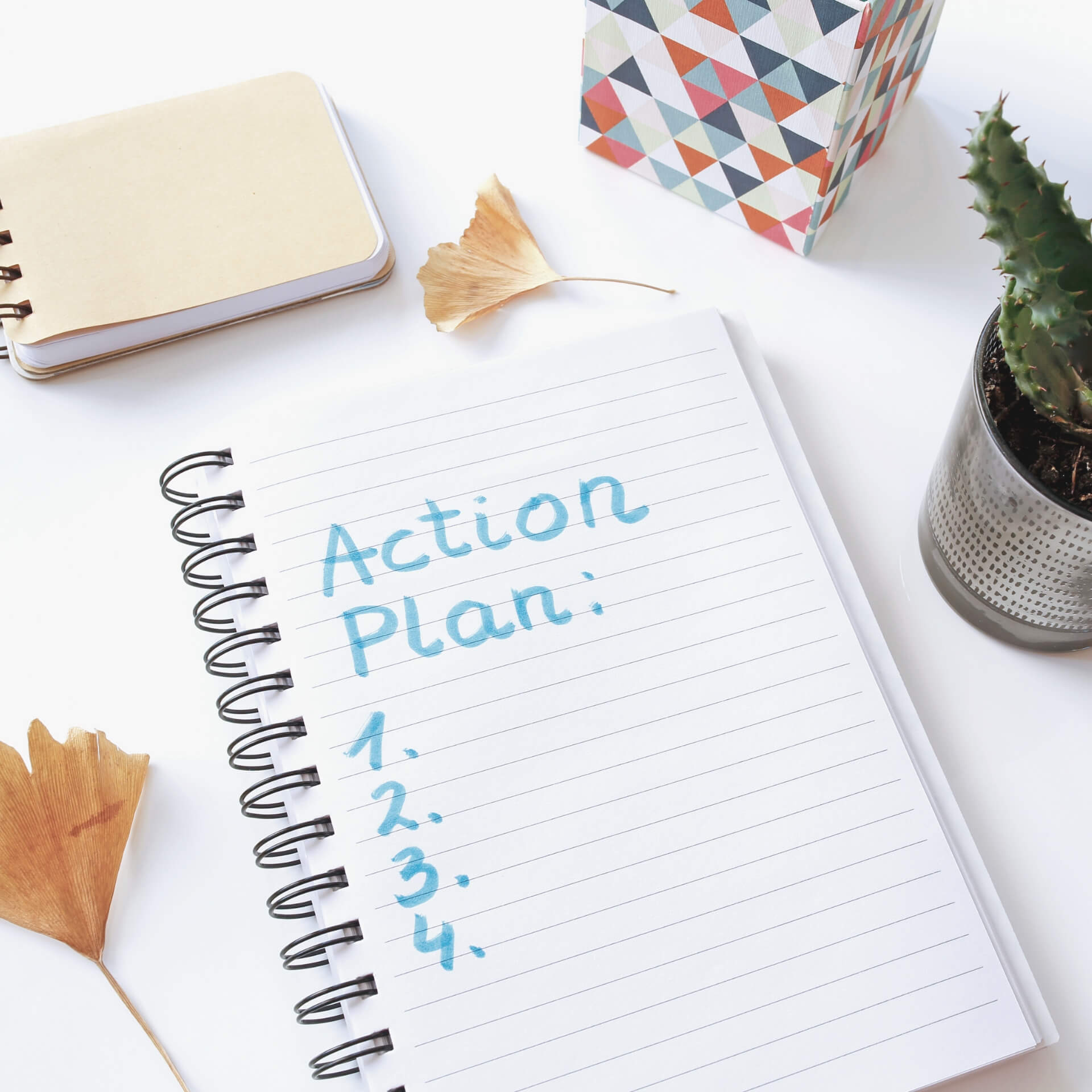 "How to Write a Blog Post: Notebook with the title ""Action Plan"" at the top and blank steps 1, 2, 3, and 4."